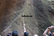 Guides explaining about edakkal caves to tourists 942
