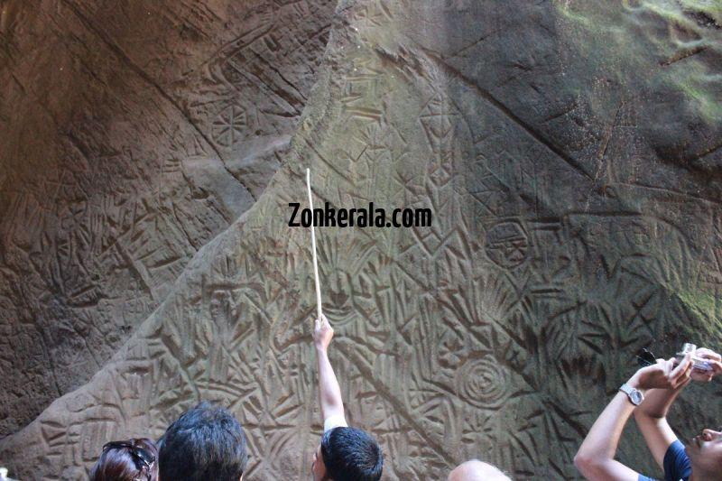 Guides explaining about edakkal caves to tourists 942